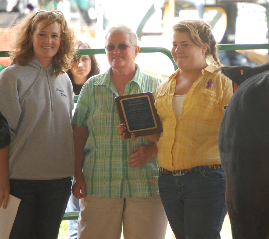 Rachel Crane (left) and Patti Herda present the William Herda Memorial Award to Jessica Meyer.