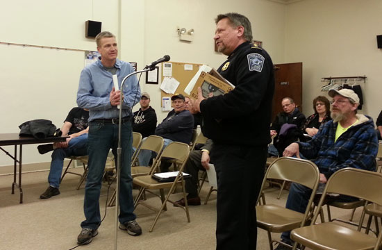 Twin Lakes Police Chief Dale Racer (right) presents Kevin Klahs, retired TLPD officer, with a plaque of appreciation at Monday's Village Board meeting.
