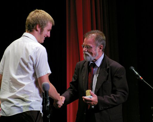 Bassist Ryan Niebuhr (left) accepts the Louis Armstrong Award from director Jack Plovanich.