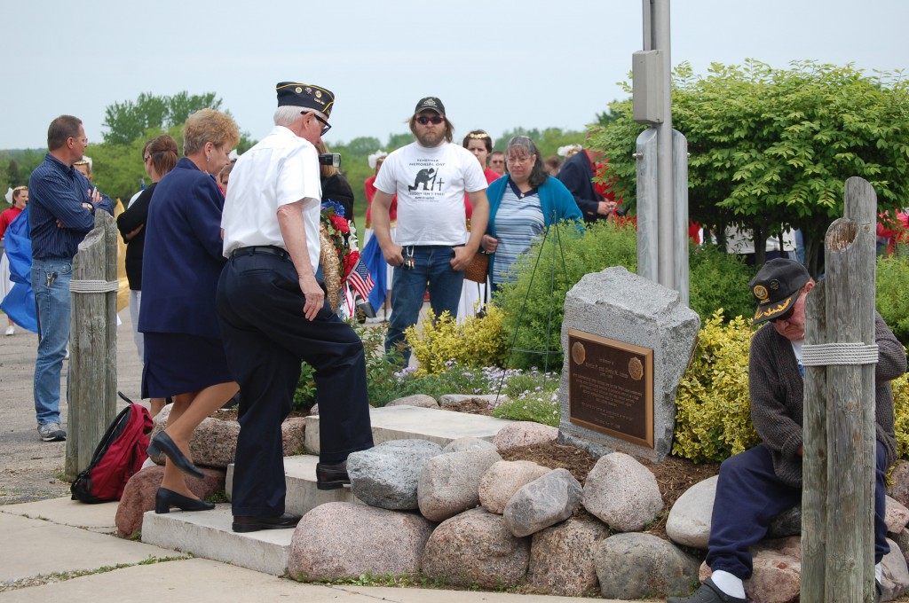 Joanne Maiter, Legion Auxiliary, and American Legion Post 544 Chaplain George Reehoff place a reef at the flagpole outside the legion hall in Legion Park.