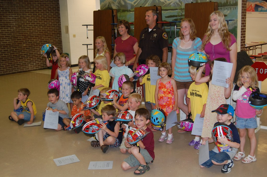 The Karen Harris Safety Town class of 2009 poses for a group photo with the instructors and Deputy Friendly, also known as Deputy Ray Rowe. They are displaying the bike helmets they received on the last day of class.