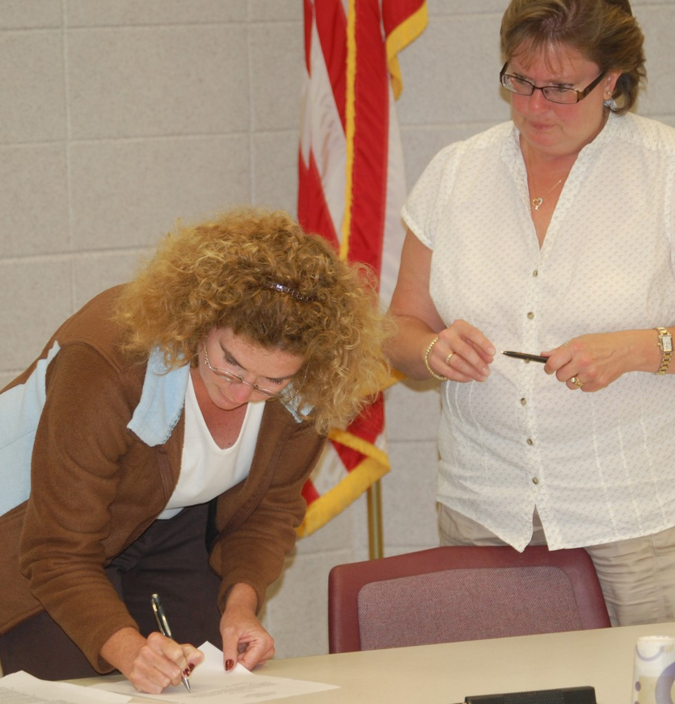 New Salem School Board member Lisa Hinze (right) signs her oath of office as board Clerk Peggy Aull looks on