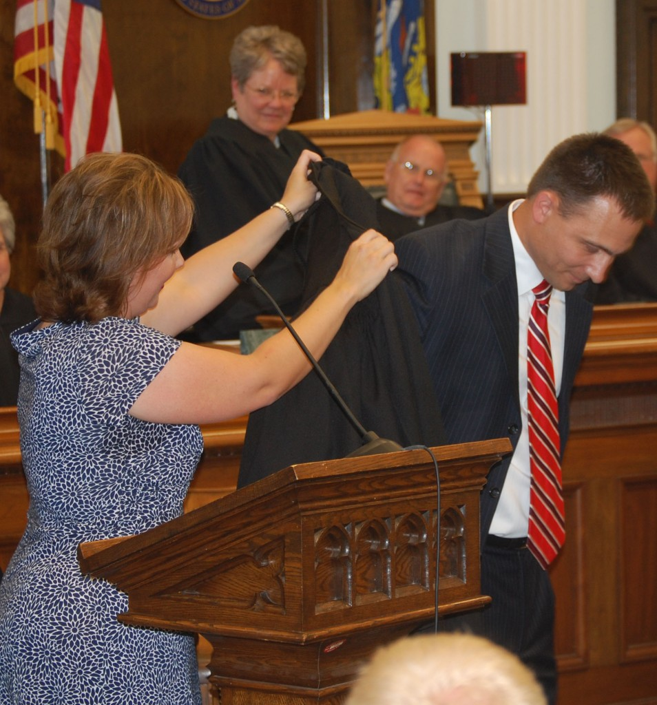 Chad Kerkman is helped into his judicial robe by his wife, state Rep. Samantha Kerkman.
