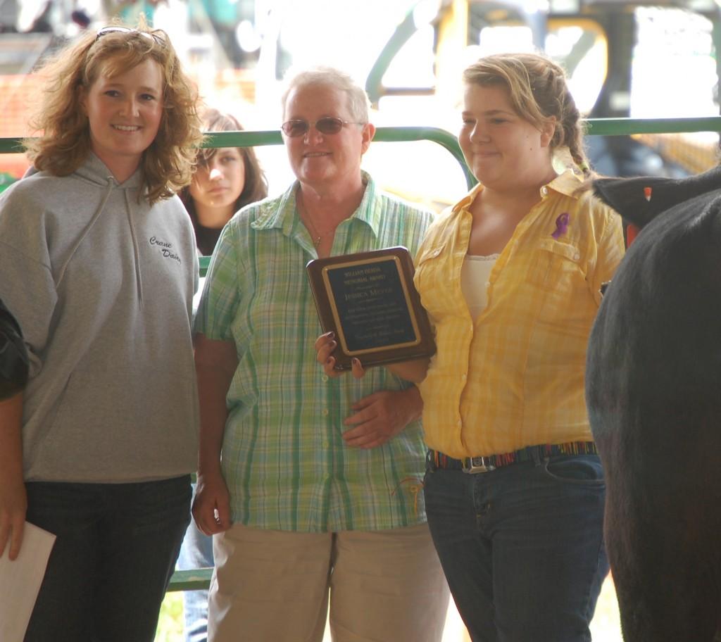 Rachel Crane (left) and Patti Herda present the William Herda Memorial Award to Jessica Meyer.