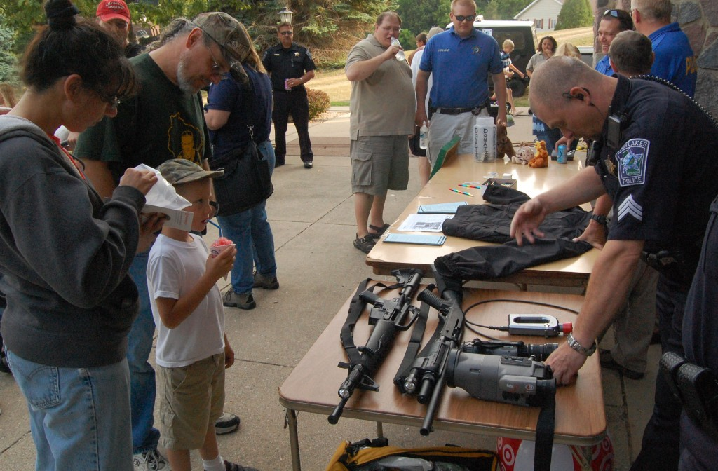 Twin Lakes police Sgt. Tim Shuda asks youngster Shane Davis which piece of equipment Shane thinks he uses the most, while Chuck Davis and Brenda Bischel look on. The right answer wasn't any of the impressive firearms on the table or even Shuda's handgun but his pen and his radio.
