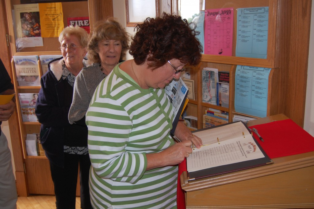 Marijo Rommelfaenger signs a register just inside the chruch door. All those attending were encouraged to sign the record, which will go in a new time capsule.