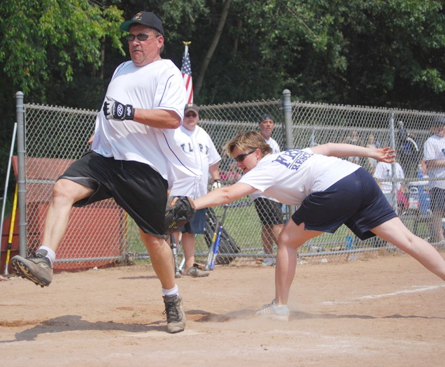 Firefighter Daniela Knoll just misses the tag on Police Chief Dale Racer on a close play at home plate. /Andrew Strother photo.