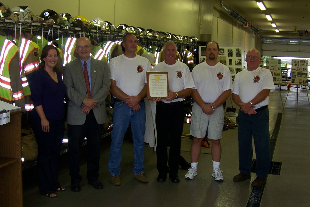 State Rep. Samantha Kerkman and state Sen. Bob Wirch (left) present Chief Stan Clause and other leaders of the Twin Lakes Fire Department with a plaque from the state legislature honoring the department on the occasion of its 80th anniversary.