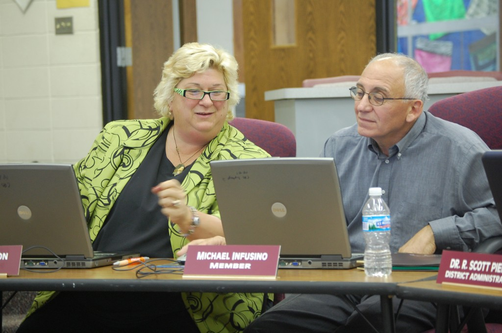 Central High School Board member Mary Anderson (left) shows board member Michael Infusino how to access materials attached to agenda items at Tuesday's School Board meeting. The board used laptops for agenda materials instead of paper for the first time Tuesday night.