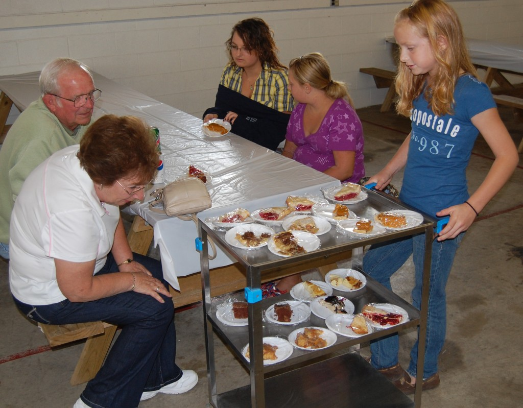 Carrie Weis (right) was one of several 4-H kids wheeling around dessert carts. Here, (clockwise from left) Barb Kruk, Don Kruk Sr., Catie Suess and Izzy Suess check out the options.