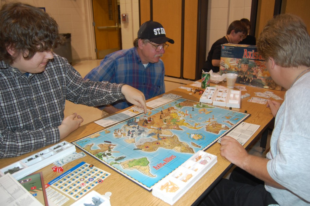 Matthew Taylor (left), John Ours and Matt Littlefiedl play a game of Axis and Allies, a board game. The three were playing the game at the Westosha Area Gaming Society booth.