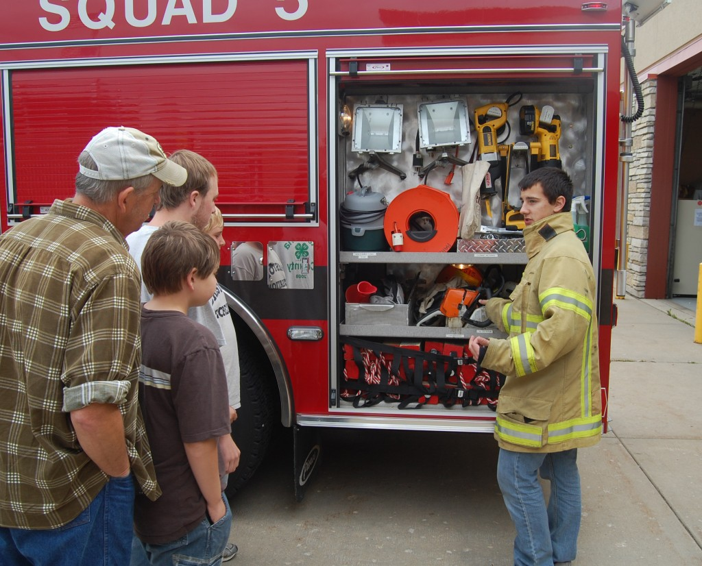 Paris firefighter Mike Jessen explains the equipment on one of the department's rigs at the department's open house Sunday.