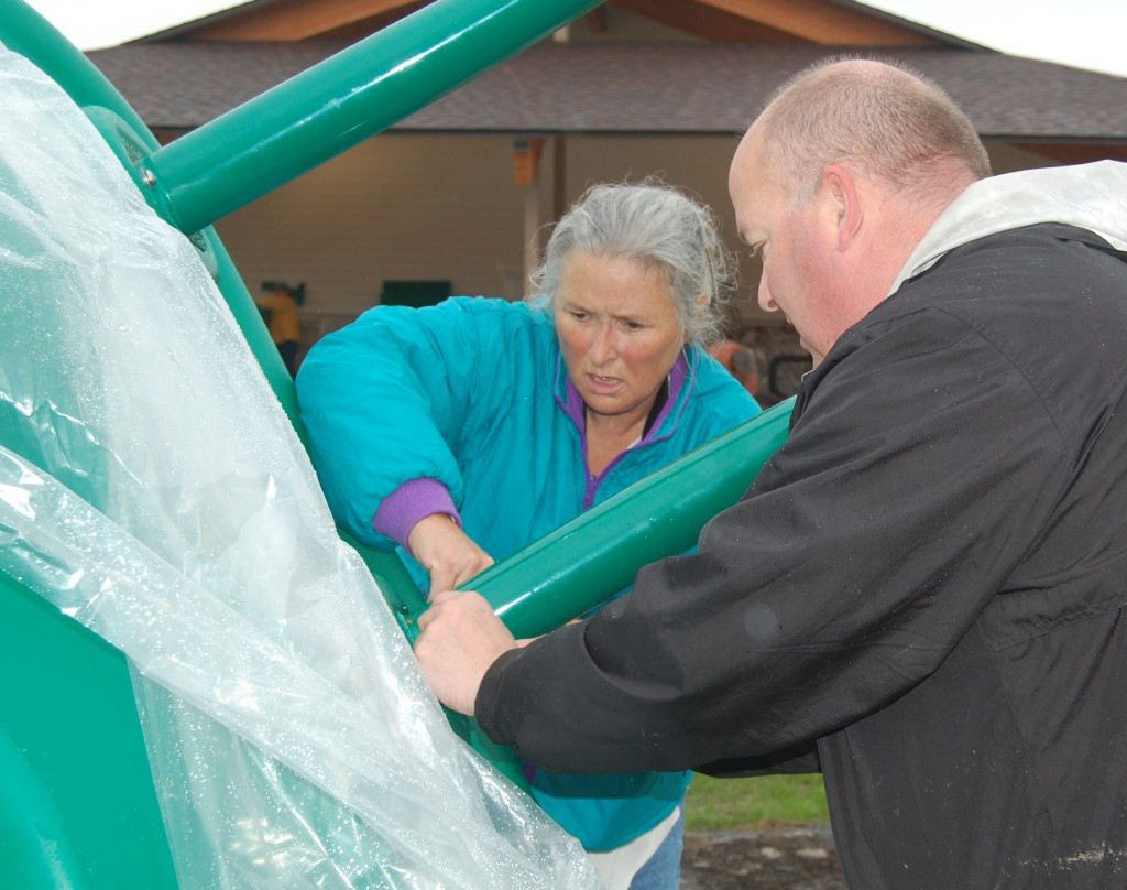 Salem town Chairman Linda Valentine and town administrator Patrick Casey work together to attach legs to a piece of equipment.