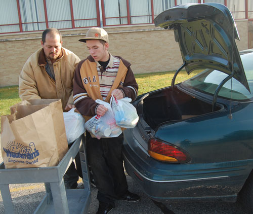 Aaron and Matthew Mountain unload a trunk of donations.