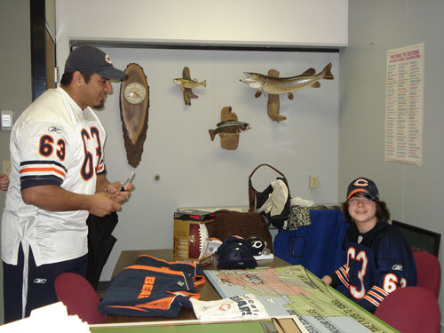 "Chicago Bear offensive lineman Roberto Garza signs some Bears items while chatting with student David Hunt at Bristol School Tuesday. Hunt was a winner in the NFL's ""Bring a Player to School"" contest. /Photo by Lisa Weiner"