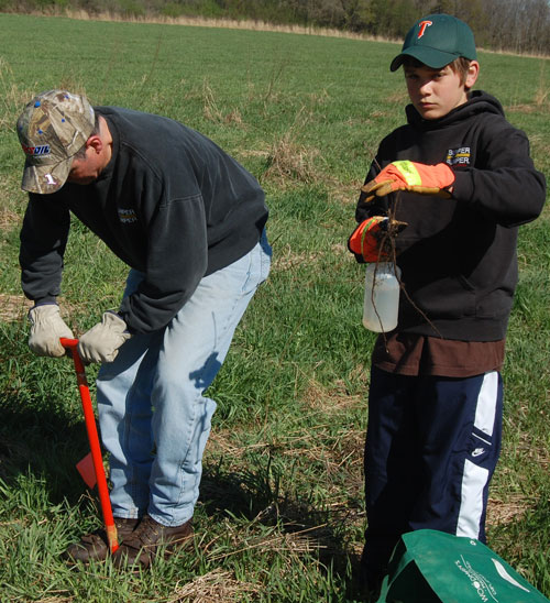 Ken Lois, left, and Marcus Lois plant a seedling.