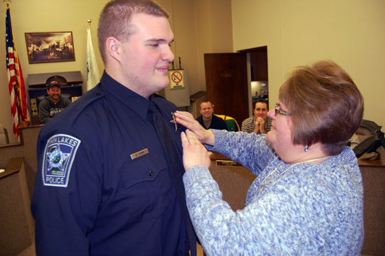 Denise Comp pins his badge on her son Jeffrey J. Comp, the latest addition to the Twin Lakes Police Department.