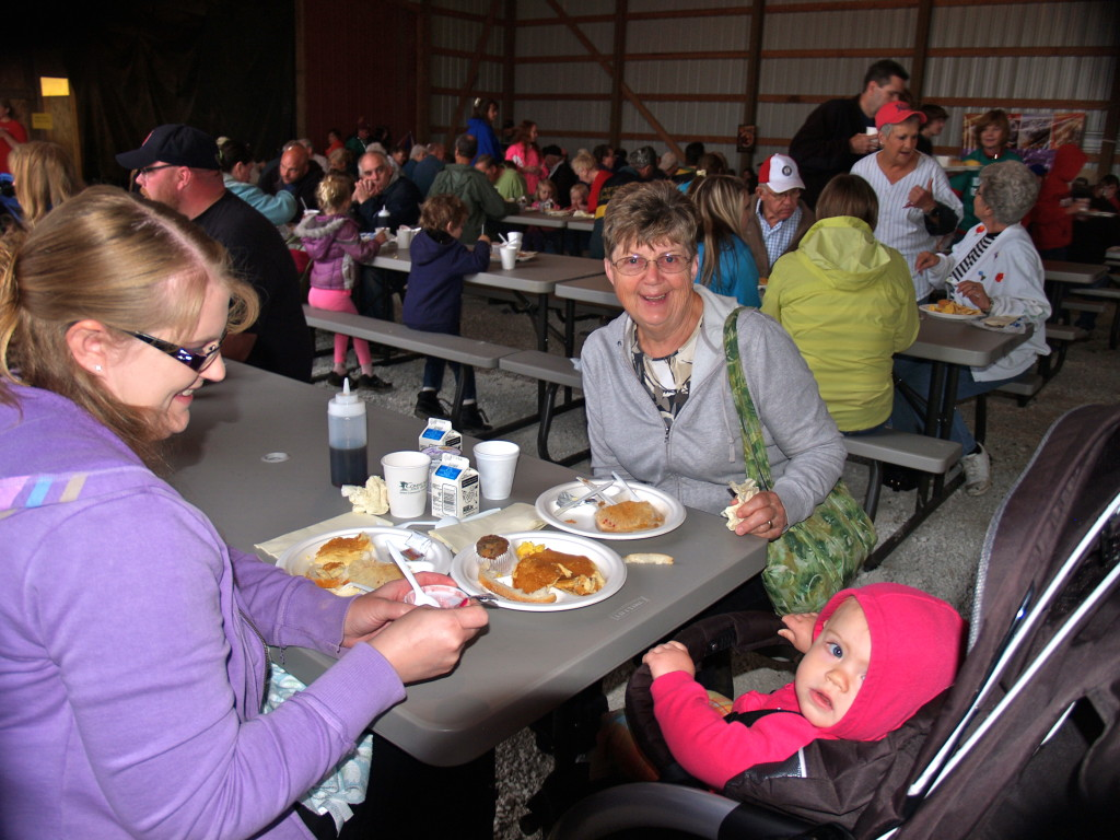 Frank Kunkel, Heidi Zavarcke, and 13-month-old Araya Zavarcke of Salem enjoy breakfast and reminiscing on farm life