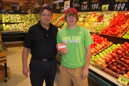 Lakeside Sentry produce manager Dave Matalas (left) presents Kyle Samples with the $100  Sentry gift card he won in westofthei.com's fair booth guessing contest.