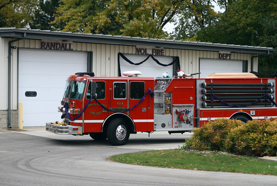 The Randall Fire Department truck carrying Thomas Brown's casket passes by Station Number 1 in Powers Lake, where Brown was the battalion chief. /Earlene Frederick photo