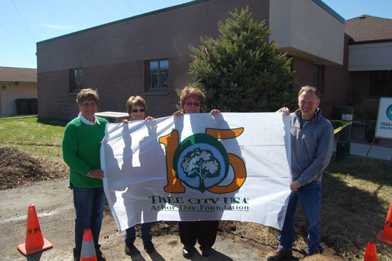(From left) Village Trustees Barbara Brenner, Gloria Walter, Kathy Christensen and village President Terry Burns display the village's new 15-year Tree City USA flag.