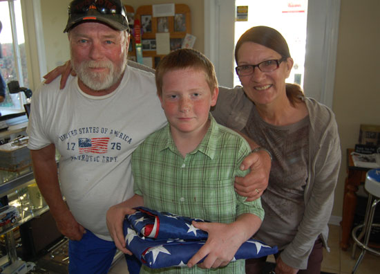 Don and Genie Mermal with Ricky Sheehan, who is holding the flags found in the gun safe Ricky's father bought in Racine.