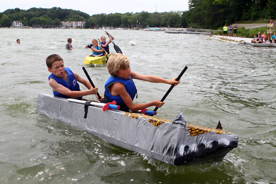 Luke Youra (9) and Ben Falardeau (9) of Twin Lakes guide their flaming shark boat back to the dock.