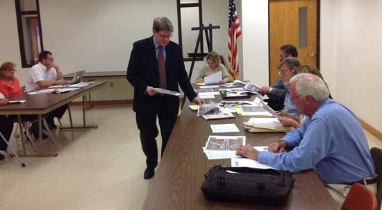 County Executive Jim Kreuser distributes information on a proposed Park and Ride lot at I-94 and Highway 142 to the Paris Town Board at a meeting Tuesday in Paris.