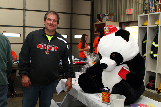 Kids could guess how many pieces of candy corn were in a jar to win the giant panda. Chief Lou Denko with the large prize.