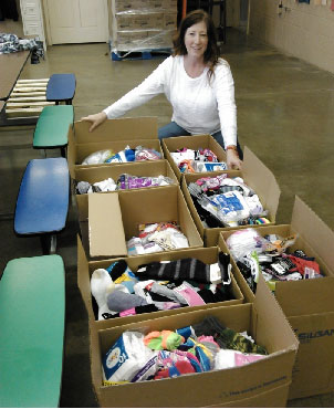 The Sharing Center's Sharon Pomaville with some of the socks collected by Western Kenosha County students. /Contributed photo