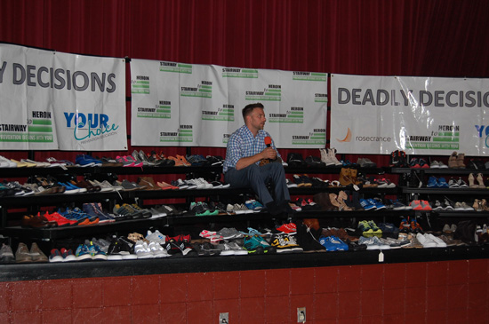 Tyler Lyberg of Your Choice Preventative Education sits among 144 pairs of empty shoes representing the deaths from heroin overdoses in Kenosha County 2013-2015.