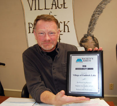 Paddock Lake President Terry Burns and the award from Society's Assets.